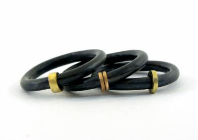 Ronde geoxideerde ringen van 3 mm. Rond de ring beweegbaar 14k rood of geelgoud bandje.