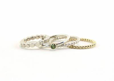 Gehamerde ring van 3 mm, een peridoot (3 mm) in een 14 k gouden zetting. De 2 parelraadringen zijn 2 mm en van zilver en 14k goud.
