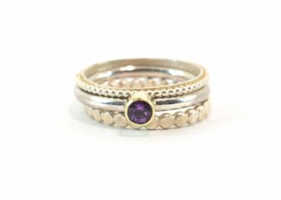 Fijne pareldraadring op bandje, een amethist in een zetting van 14k goud op gladde ronde band. Gehamerde ring van 2.5 mm. De ringen zijn van zilver.