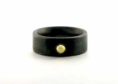 Een stoere, zwart gerhodineerde ring van zilver. reedte 8 mm. In het midden is een 14k goud balletje geplaatst..