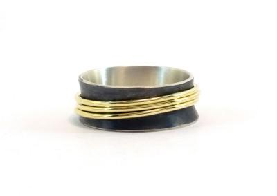 De ring is 8 mm breed, licht concaaf en zwart gerhodineerd. De 14k gouden ringetjes bewegen hiertussen.